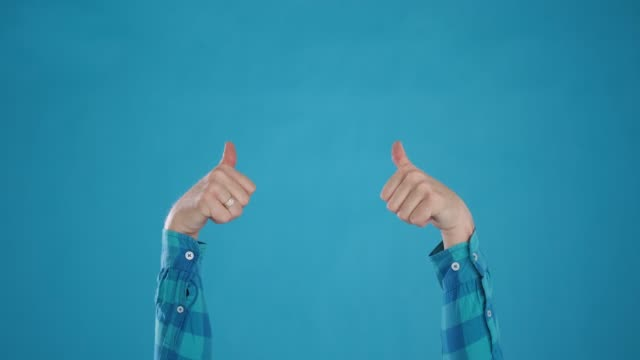 caucasian hands show cool,thumbs up,ok,on blue background close-up - thumbs up стоковые видео и кадры b-roll