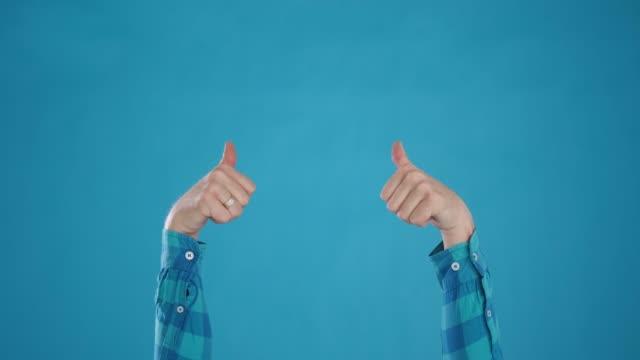 kafkas elleri serin, başparmak yukarı, tamam, mavi arka plan yakın çekim göstermek - thumbs up stok videoları ve detay görüntü çekimi