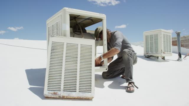 vídeos y material grabado en eventos de stock de un manero caucásico en sus cuarenta aplica la cinta de plomeros blancos al interior de un refrigerador del pantano de la azotea mientras lo prepara para su uso en un día soleado - fontanero