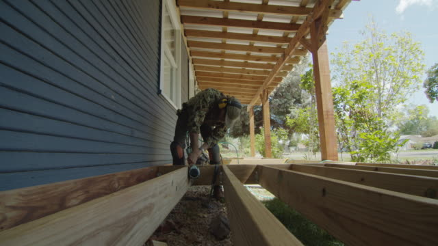 A Caucasian Handyman in His Forties Wearing a Hat, Hearing Protection, and Kneepads Uses a Pneumatic Nail Gun to Secure Metal Corner Brackets on Wooden Boards while Building a Deck in a Residential Neighborhood Outdoors on a Sunny Day