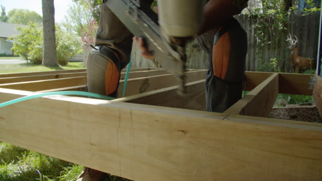 a caucasian handyman in his forties wearing a hat, hearing protection, and kneepads uses a pneumatic nail gun to position a wooden board and then uses it to secure the board into place then uses a hammer while building a deck in a residential neighborhood - nail work tool stock videos & royalty-free footage