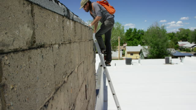 A Caucasian Handyman in His Forties with a Beard and a Backpack Climbs up a Ladder on a Roof on a Sunny Day