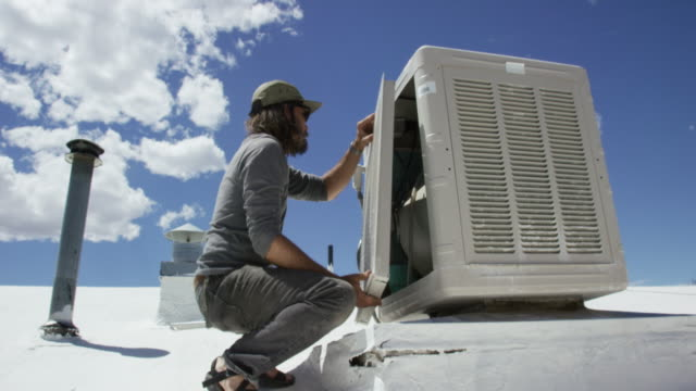A Caucasian Handyman in His Forties with a Beard Replaces the Side Panel of a Swamp Cooler on a Rooftop on a Sunny Day