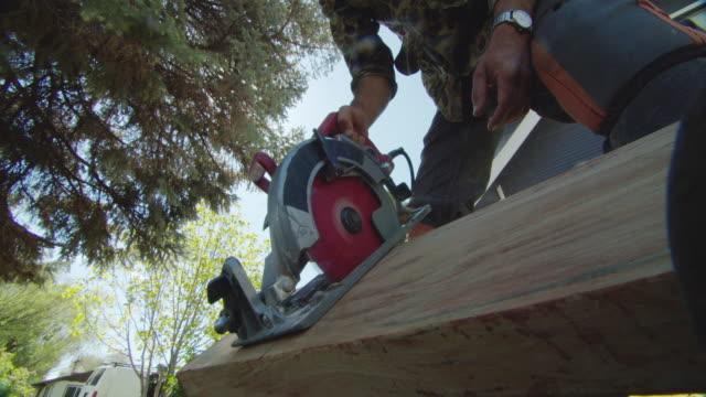 ein kaukasischer handyman wearing kneepads benutzt eine kreisförmige säge, um ein holzbrett in einer wohngegenwart im freien an einem sonnentag zu schneiden - kreissäge stock-videos und b-roll-filmmaterial