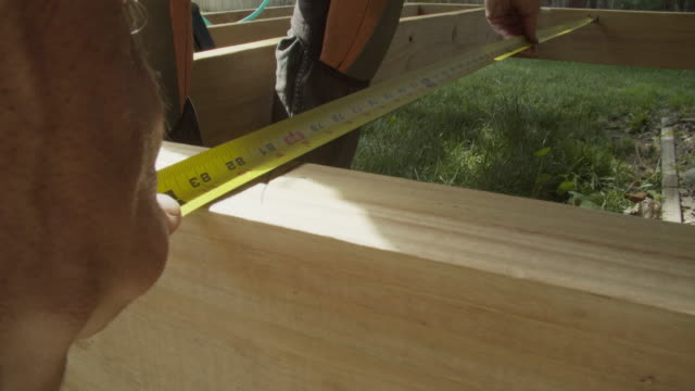 A Caucasian Handyman Wearing Kneepads Uses a Tape Measure to Measure the Space Between Wooden Boards While Building a Deck in a Residential Neighborhood Outdoors on a Sunny Day