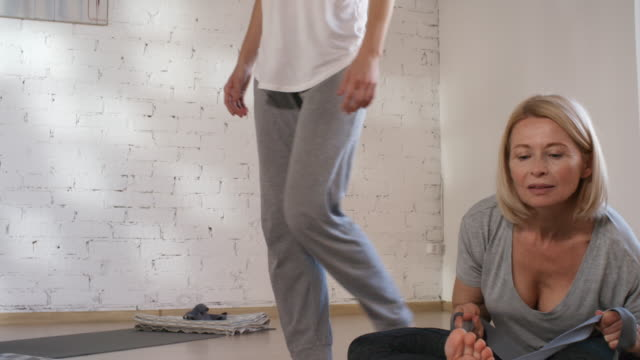 Caucasian Husband and Wife Doing Yoga Together in Studio Medium panning shot of smiling female yoga teacher in mid-twenties giving private class for middle-aged Caucasian man and woman, walking around studio and manually correcting their postures prop stock videos & royalty-free footage