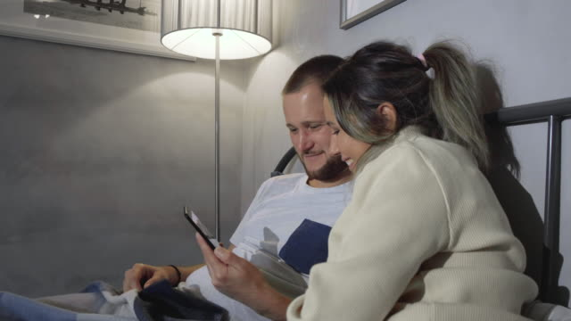 Caucasian husband and wife in pyjamas sitting up silently in bed at night, leaning on headboard, holding smartphones and looking completely immersed