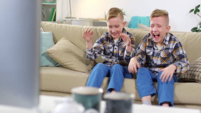 vídeos de stock e filmes b-roll de caucasian identical twins watching tv and laughing hysterically - tv e familia e ecrã