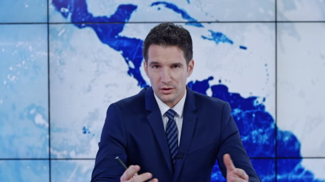 LD Caucasian male anchor presenting the news Medium locked down shot of a Caucasian male news anchor giving the latest news report on the evening broadcast. Shot in Slovenia. journalist stock videos & royalty-free footage