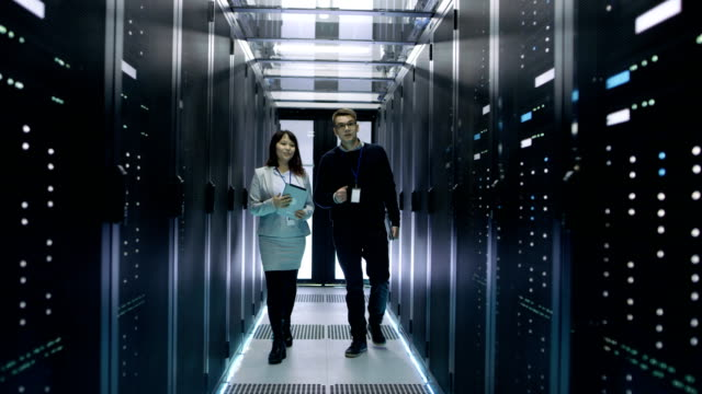 Caucasian Male and Asian Female IT Technicians Walking in Data Center with Rows of Rack Servers. They Have Discussion, She Holds Tablet Computer. video