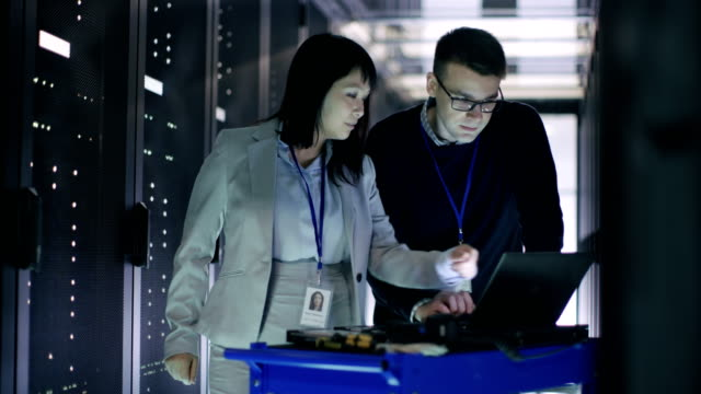 Caucasian Male and Asian Female IT Technicians Working with Crash Cart Laptop in Big Data Center full of Rack Servers.