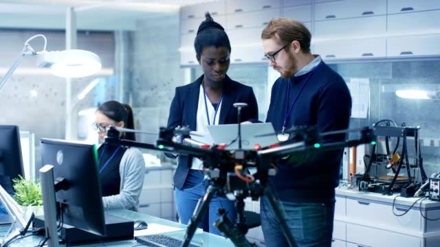 백인 남성과 검은 여성 엔지니어 노트북의 도움과 메모를 복용 드 론 프로젝트에서 작업. 그는 밝은 현대 하이테크 실험실에서 작동 합니다. - 무인항공기 스톡 비디오 및 b-롤 화면