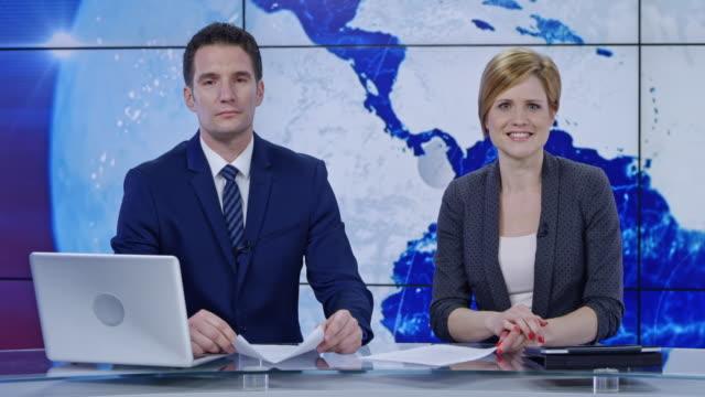 vidéos et rushes de ld caucasienne mâles et femelles d'ancrage présentant les nouvelles - interview