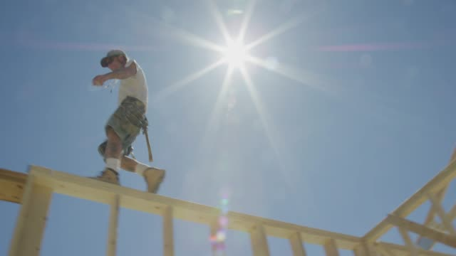 A Caucasian Male Construction Worker in His Forties Balances While Walking Across the Top of a Framed House on a Clear, Sunny Day with a Hydraulic Crane in the Background