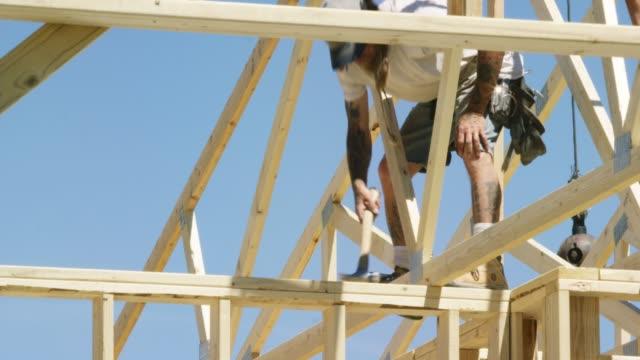 vídeos y material grabado en eventos de stock de un trabajador de la construcción del macho caucásico en sus cuarenta asegura un techo de madera truss a una estructura con un martillo y clavos mientras enmarca una casa en un día despejado y soleado - imperfección