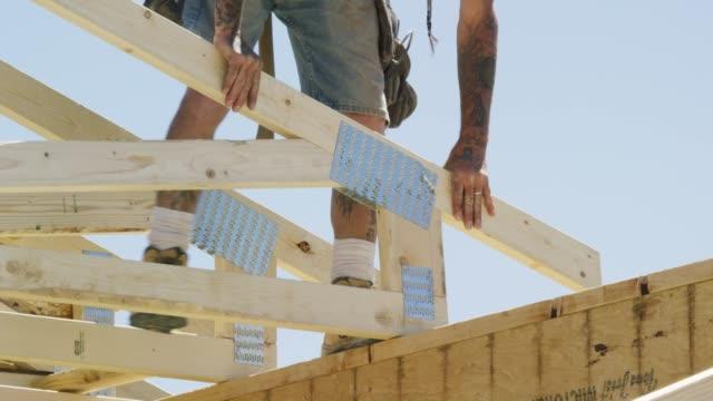 en kaukasiska manliga byggnads arbetare i fyrtioårsåldern med tatueringar säkrar en inramad trä tak truss till ett hus med en hammare och naglar på en klar, solig dag - hammare bildbanksvideor och videomaterial från bakom kulisserna