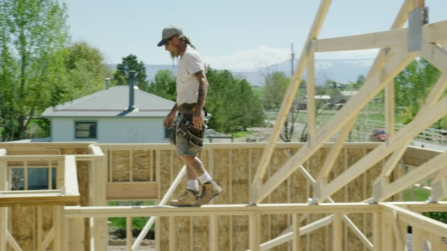 A Caucasian Male Construction Worker in His Forties with Tattoos Balances While Walking Across the Top of a Framed House on a Clear, Sunny Day with a Hydraulic Crane in the Background