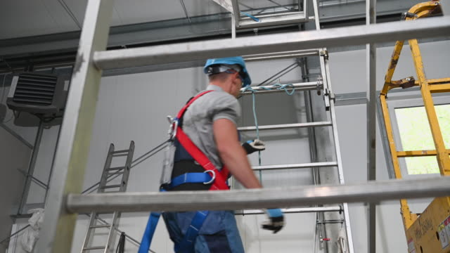 caucasian male contractor climbing up tall metal ladder wearing protective harness and hard hat. - imbracatura video stock e b–roll