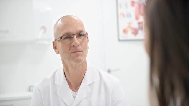 Caucasian male doctor listening to his patient in his office Medium handheld shot of a Caucasian male doctor sitting in his office and listening to the female patient. Shot in Slovenia. mid adult stock videos & royalty-free footage