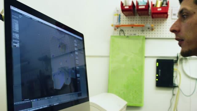 un ingegnere maschile caucasico ruota una parte progettata in 3d (cad) su uno schermo di computer per la stampa 3d - industria elettronica video stock e b–roll