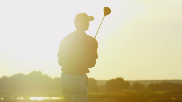 Caucasian male golfer on golf course at sunset video