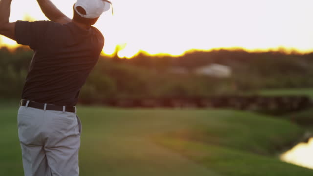 Caucasian male golfer teeing off green at sunset video