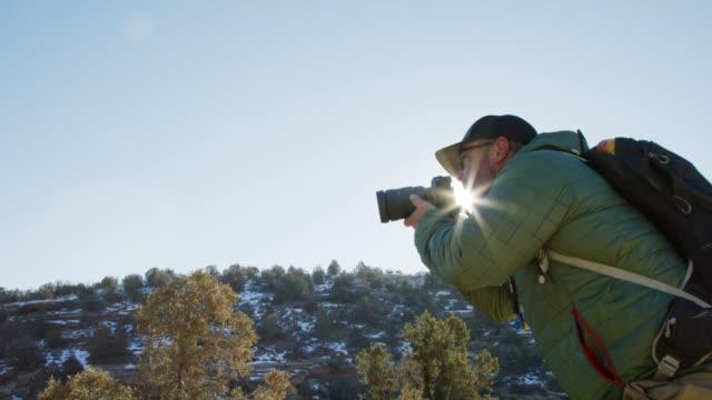 vidéos et rushes de un photographe mâle caucasien dans ses quarantaine vêtu de matériel de randonnée prend des photographies dans le haut désert du colorado occidental en hiver (près du colorado national monument-grand junction, colorado) - verre optique