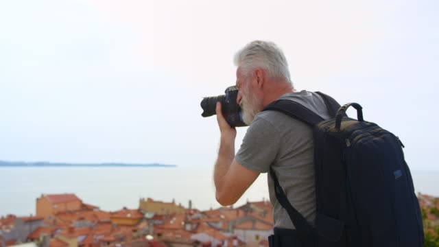 Caucasian male photographer with grey hair and beard taking photos on a path above the picturesque coastal town