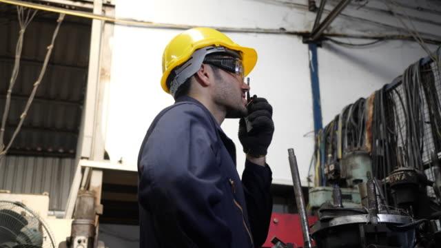 caucasien manlig professionell ingenjör bär hård hatt talar med walkie talkie kontroller arbete i en fabrik. - kommunikationssätt bildbanksvideor och videomaterial från bakom kulisserna