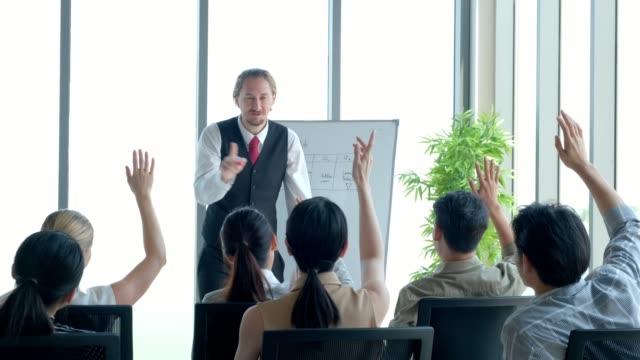 白人男性プロジェクトリーダーは、創造的なチームのための会議のプレゼンテーションを開催します。彼はビジネスプランニングコンセプトのためのインタラクティブホワイトボードデバイ� - 研修点の映像素材/bロール