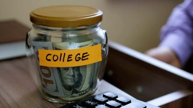 caucasian male putting a glass jar put in a drawer  table with his savings for future college - długi filmów i materiałów b-roll