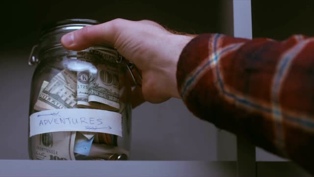 RL DOLLY Caucasian male putting a glass jar with his savings for future travels video