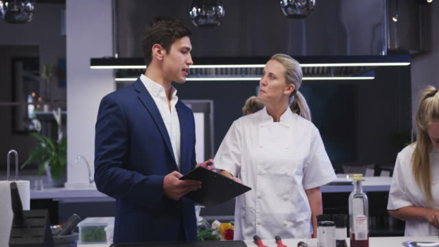 caucasian male restaurant manager in the kitchen talking to a caucasian female cook, giving instruct - busy restaurant kitchen stock videos & royalty-free footage