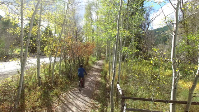 Caucasian male rides a bicycle on mountain trail next to a two-lane road