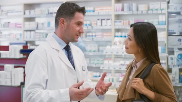 Caucasian male salesperson advising an Asian woman about a vitamin supplement