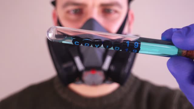 Caucasian Male Scientist Wearing Gas Mask and Blue Latex Gloves while Examining Test Tube With Covid 21 Sample