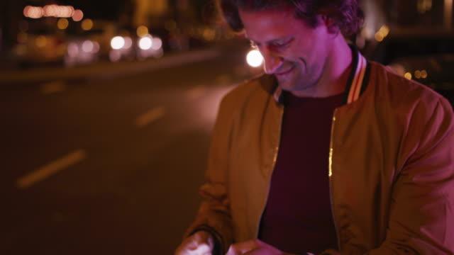 백인 남성 미소와 저녁에 거리에서 전화에 이야기 - 중년 남자 스톡 비디오 및 b-롤 화면