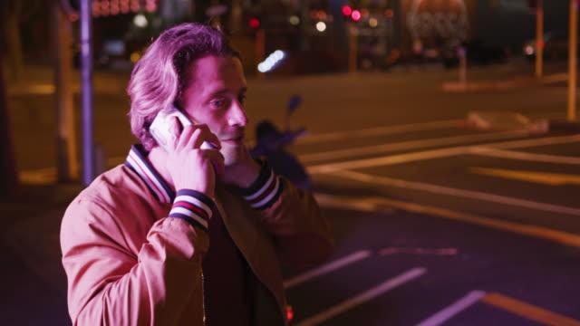 백인 남성 미소와 저녁에 전화에 이야기 - 중년 남자 스톡 비디오 및 b-롤 화면