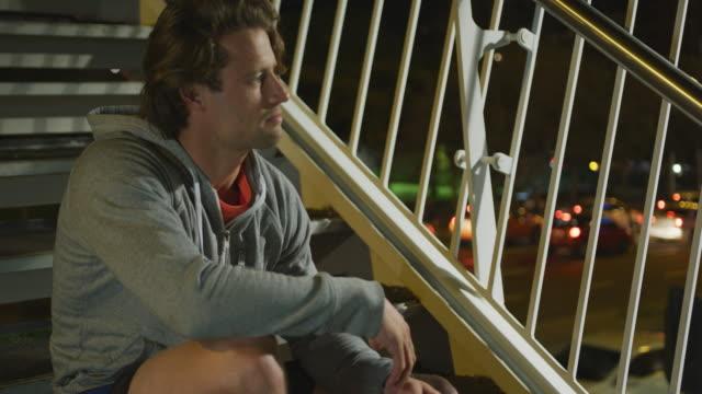 백인 남성 미소와 저녁에 계단에 자신의 레이스를 묶어 - 중년 남자 스톡 비디오 및 b-롤 화면
