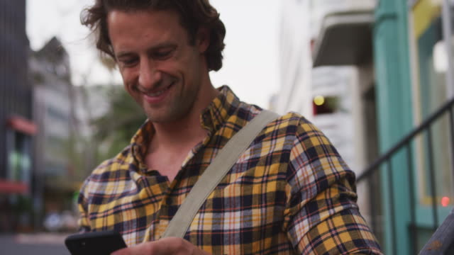 Caucasian male smiling and using his phone in a street Caucasian man wearing a checkered shirt, out and about in the city streets during a day, leaning on a handrail and using his smartphone and smiling. mid adult men stock videos & royalty-free footage