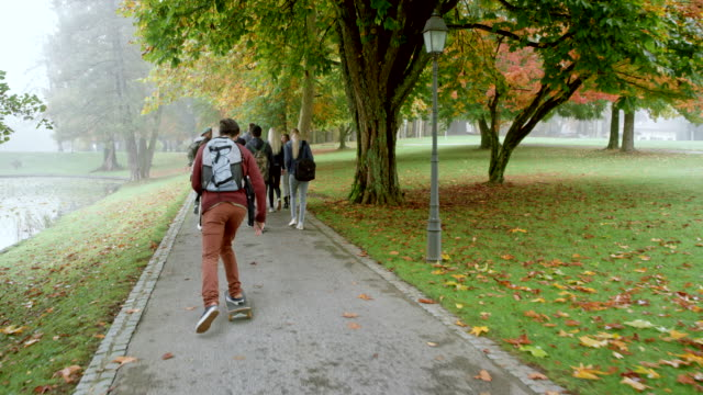 Caucasian male student riding his skateboard past a group of student walking through a park on a fall morning Wide right behind handheld shot of a young Caucasian man riding his skateboard past a group of students walking in the park on a foggy fall morning. Shot in Slovenia. campus stock videos & royalty-free footage