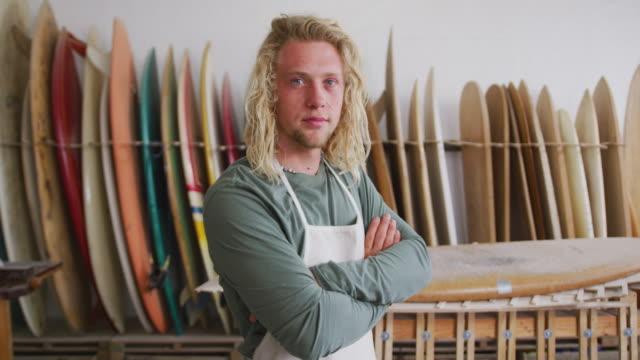 caucasian male surfboard maker wearing a protective apron with arms crossed - sprzęt sportowy filmów i materiałów b-roll