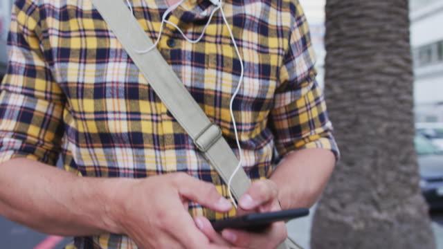 백인 남성 이야기 하 고 거리에서 자신의 휴대 전화를 사용 하 여 - 중년 남자 스톡 비디오 및 b-롤 화면