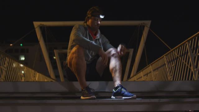 백인 남성은 헤드 램프를 입고 저녁에 계단에 자신의 레이스를 묶는 - 중년 남자 스톡 비디오 및 b-롤 화면