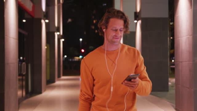 이어폰과 스케이트보드를 입고 웃고 걷고, 거리에서 휴대폰을 사용하는 백인 남성 - 중년 남자 스톡 비디오 및 b-롤 화면