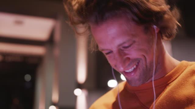 백인 남성은 저녁에 거리에서 자신의 휴대 전화를 사용하여, 미소, 이어폰을 입고, 미소 - 중년 남자 스톡 비디오 및 b-롤 화면