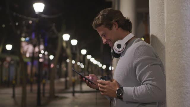 저녁에 자신의 휴대 전화를 사용하여 헤드폰을 착용하고 마시고, 마시는 백인 남성 - 중년 남자 스톡 비디오 및 b-롤 화면