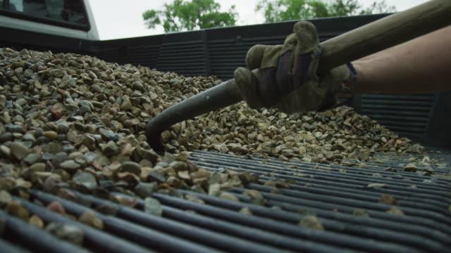 ein kaukasischer männlicher tragen schals felsen aus der rückseite seines pick-up-leckens mit einem metallschaufel outdoor - gärtnerisch gestaltet stock-videos und b-roll-filmmaterial
