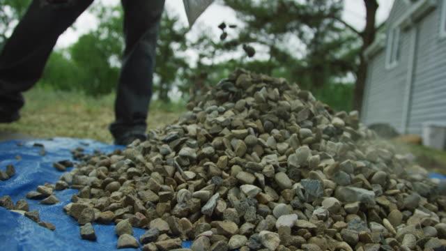 ein kaukasischer männlicher tragen schals felsen aus der rückseite seines pick-up-leckens mit einem metallschaufel und dumps them auf einem blue tarp neben einem haus draußen - gärtnerisch gestaltet stock-videos und b-roll-filmmaterial