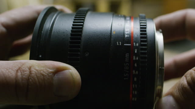 A Caucasian Man Adjusts the Manual Aperture Ring on a 85mm T1.5 Lens (Adjusts T Stop / F Stop)
